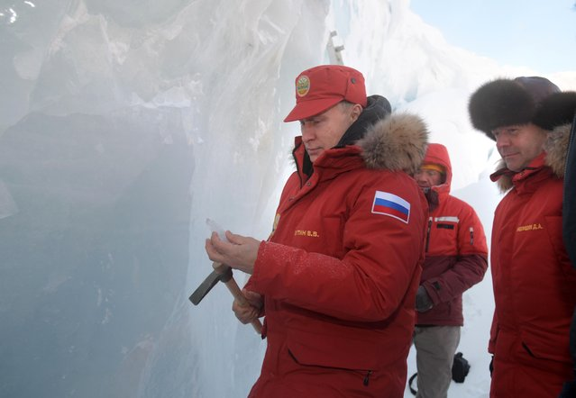Russian President Vladimir Putin, center, and Prime Minister Dmitry Medvedev, right, inspect a cavity in a glacier on the Franz Josef Land archipelago in Arctic Russia, Wednesday, March 29, 2017. Russia has sought to strengthen its foothold in the Arctic amid intensifying rivalry for the region's rich natural resources between polar countries. (Photo by Alexei Druzhinin, Sputnik, Kremlin Pool Photo via AP Photo)