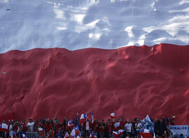 A giant Chile flag is held over fans before their Copa America 2015 final soccer match against Argentina at the National Stadium in Santiago, Chile, July 4, 2015. (Photo by Marcos Brindicci/Reuters)