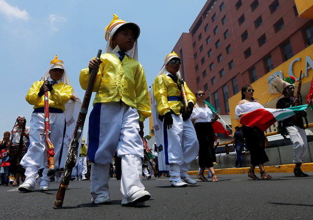 A boy and other people wearing a period costume re-enacts the battle of Puebla, take part along the streets in the Penon de los Banos neighbourhood of Mexico City, Mexico May 5, 2016. (Photo by Henry Romero/Reuters)