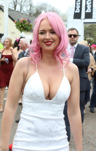 A pink-haired partygoer flashed her cleavage in a low-cut, tight-fitting white strappy dress during the Grand National Festival at Aintree Racecourse on April 7, 2017 in Liverpool, England. (Photo by WENN)