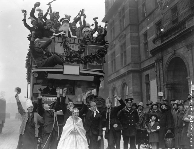 1926: Children from the Royal Caledonian School enjoying a festive Christmas pageant on an open top bus which is carrying Santa and his helpers through the streets