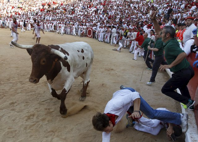 A runner dives to avoid a steer in the bullring following the first running of the bulls of the San Fermin festival in Pamplona, northern Spain, July 7, 2015. (Photo by Joseba Etxaburu/Reuters)