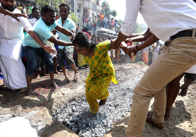 A Hindu devotee is helped by other people as she walks on burning coals during a religious procession Vel Festival of the Hindu goddess Maha Mariamman (Sheetla Mata), in New Delhi, India, 06 April 2017. People get their bodies pierced with different kinds of metal needles and rods and participate in a religious procession as thanks giving gesture to the goddess in return of their fulfilled wishes during the annual procession. (Photo by Rajat Gupta/EPA)