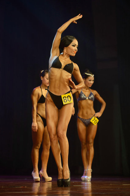 """In a photo taken on September 15, 2013, amateur """"body fitness"""" competitors from China pose on stage during a bodybuilding contest in Zhengzhou, Henan province. More than 20 professionals – including a dozen from China – were competing in the Bodybuilding Grand Prix in the central Chinese city for a top prize worth 80,000 yuan (13,000 USD). They were joined by scores of amateurs from across the country, in what event organisers said was a sign of the increasing popularity of muscle building in China. (Photo by Ed Jones/AFP Photo)"""