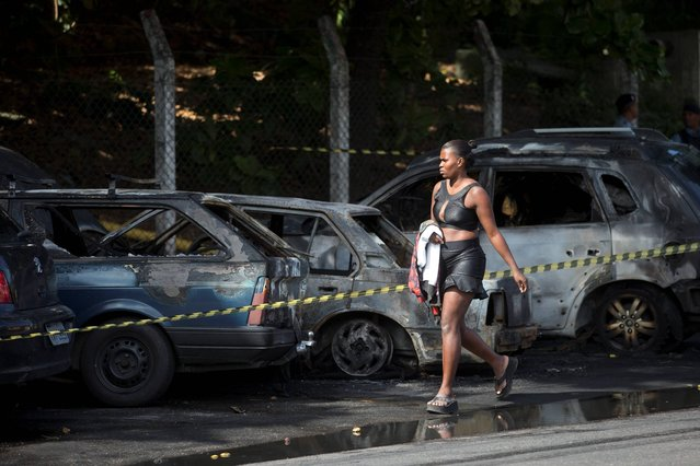 A woman walks past three cars that were set on fire by protestors demonstrating against the death of an elderly woman who died yesterday during a police operation against suspected drug traffickers in the Complexo do Alemao of Rio de Janeiro, Brazil, Monday, April 28, 2014. The woman who died is Arlinda Bezerra das Chagas, age 72. (Photo by Silvia Izquierdo/AP Photo)