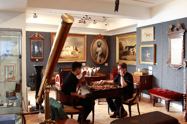 Bonhams employees Tim Lee (L) and and Damien Mabardi (R) play on a Louis XV/XV1 Macassar Ebony and Ivory inlaid Tric Trac table