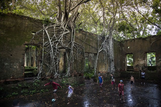 Young people play football in the ruins of the building Belisario Penna, located in the village of Paricatuba, about 35 km from Manaus, Amazonas, Brazil, crossing the bridge over the Negro River, on May 9, 2014. The building, built in 1898, served to host Italian immigrants but a few years later – in 1906 – it housed the institute Afonso Pena, a shelter for lepers. Currently, only the ruins of the building remain there and the place is an attraction for tourists, while for the residents of Paricatuba, it works as a space for football and leisure. (Photo by Raphael Alves/AFP Photo)