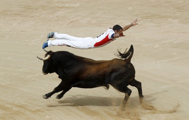 """A """"recortador"""" jumps over a bull during a contest at Pamplona's bullring on the sixth day of the San Fermin festival, northern Spain, July 11, 2015. The """"recortadores"""" dodge bulls without a cape or sword. (Photo by Joseba Etxaburu/Reuters)"""