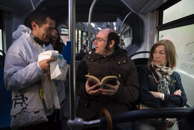 "A passenger of the public bus company of San Sebastian receives a book from a volunteer (L) during a bus trip in the Spanish Basque city of San Sebastian on May 13, 2016. During the celebrations of San Sebastian as European capital of culture 2016, Donostia Kultura and San Sebastian's public transport Dbus company have launched the initiative ""A book, a trip"" that gifts with a book and a free bus trip to those users who read as they travel. (Photo by Ander Gillenea/AFP Photo)"