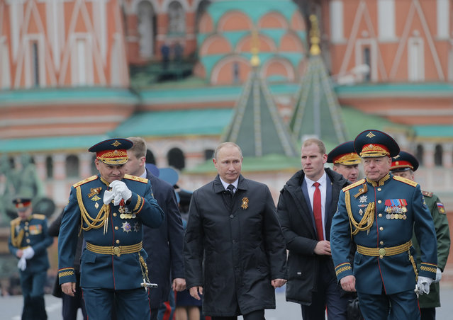 Russian Defence Minister Sergei Shoigu, left, Russian President Vladimir Putin, center, and Russian army Gen. Oleg Salyukov, right, walk along the Red Square during the Victory Day military parade to celebrate 72 years since the end of WWII and the defeat of Nazi Germany, in Moscow, Russia, on Tuesday, May 9, 2017. (Photo by Yuri Kochetkov/Pool Photo via AP Photo)