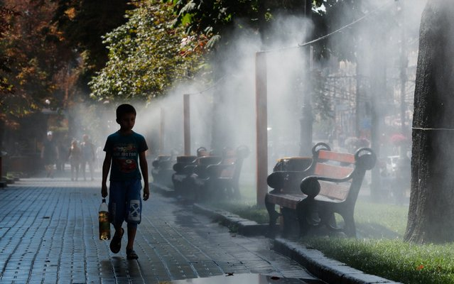 Ukrainians cool themselves during a hot day with drops of water which is sprayed from a pipe hanging over a sidewalk of the central street of Khreshchatyk in Kiev, Ukraine, 12 August 2019. (Photo by Sergey Dolzhenko/EPA/EFE)