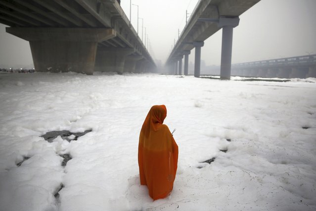 In this Saturday, November 2, 2019, file photo, an Indian Hindu devotee performs rituals in the Yamuna river, covered with chemical foam caused by industrial and domestic pollution, during Chhath Puja festival in New Delhi, India. Schools have reopened in the Indian capital with toxic air level coming down by more than half since authorities declared a health emergency last Friday.  Authorities are tackling a large amount of toxic foam floating in the Yamuna River, caused partly by high ammonia levels emanating from industrial pollutants. (Photo by Altaf Qadri/AP Photo/File)