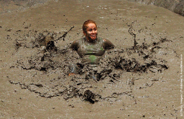 Competitors crawls through a mud pit under barbed wire as he competes in The Tough Bloke Challenge in Melbourne, Australia