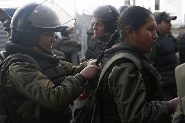Women police in full riot gear braid each others hair before clashes with protesting miners from Bolivia's Potosi region, in La Paz, Bolivia, Wednesday, July 22, 2015. (Photo by Juan Karita/AP Photo)