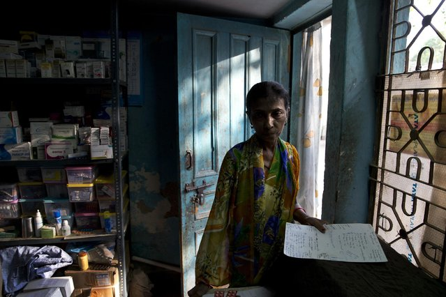 """In this June 8, 2015 photo, a patient waits with a doctor's prescription to receive free medicine from Omkarnath, who goes by the name """"Medicine Baba"""", in New Delhi, India. (Photo by Saurabh Das/AP Photo)"""