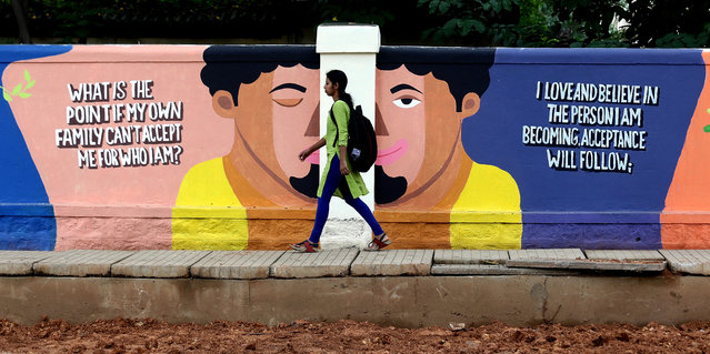 An Indian walks next to a painting on a roadside wall in Bangalore, India, 18 September 2019. Around 250 artists painted the walls with different vibrant color to create awareness about suicide prevention and mental health among people, as part of the World Suicide Prevention Day. (Photo by Jagadeesh N.V./EPA/EFE)