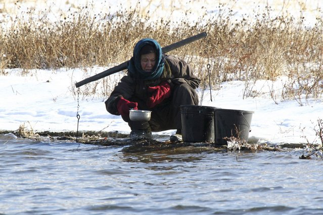 A North Korean woman fills buckets with water after snowfall along the banks of the Yalu River, near the North Korean Sakchu County, December 17, 2014. Picture taken on the China side of the Yalu River. (Photo by Jacky Chen/Reuters)