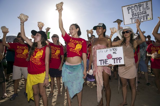 Protestors gather on the beach near the hotel where the Trans-Pacific Partnership (TPP) meeting is being held in Lahaina, Maui, Hawaii July 29, 2015. The protestors tried to break a world record by having more than two hundred people blow conch shells at once. (Photo by Marco Garcia/Reuters)