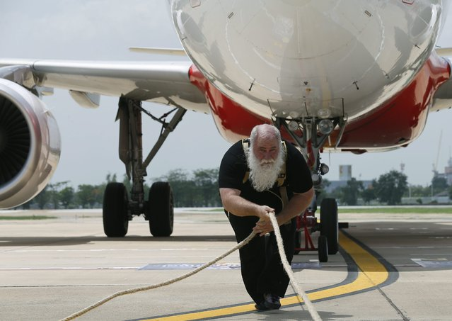 The strongest man in the world record attempt for the heaviest plane pulled, Canadian Kevin Fast, 51, pulls an Airbus A320-200 (180 seats) weighing 65 tonnes, a distance of 20 m. with a time of 0.53 minute, during a exclusive show at the Don Mueang International Airport in Bangkok, Thailand, 27 June 2014. (Photo by Narong Sangnak/EPA)