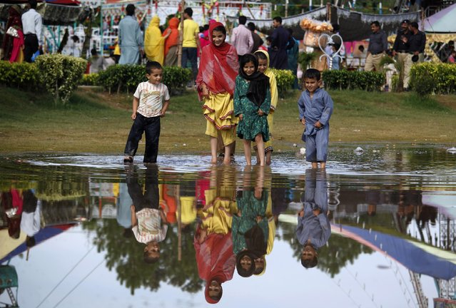 Pakistani children play in a puddle caused by heavy rain at a park in Rawalpindi, Pakistan, Tuesday, July 21, 2015. (Photo by Anjum Naveed/AP Photo)