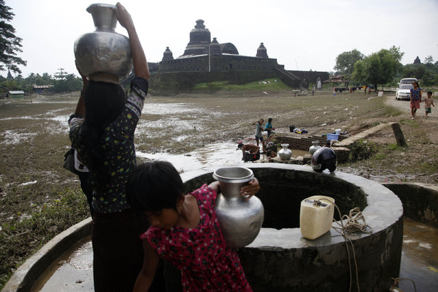 Local residents fetch water  at a well near a pagoda in Myauk U, Rakhine State, western Myanmar, Tuesday, August 4, 2015. (Photo by Khin Maung Win/AP Photo)