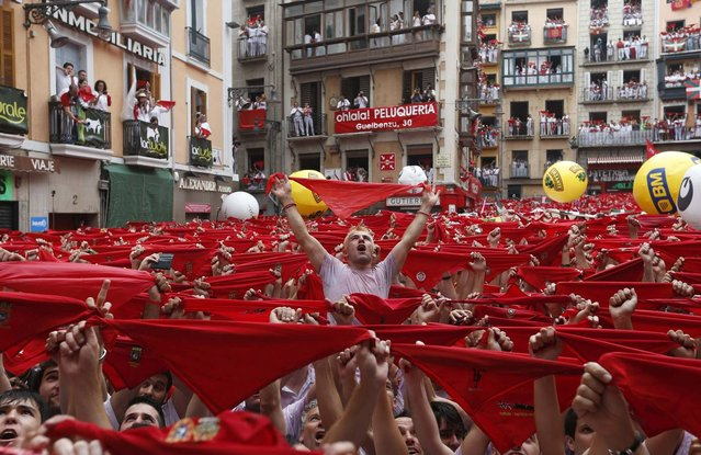 """Thousands of revellers hold up their red scarfs as the rocket fire or """"Txupinazo"""" marks the start of the Festival of San Fermin (or Sanfermines) at Consistorio square in Pamplona, Spain, 06 July 2014. The annual nine day long running-with-the-bulls fiesta commemorates St. Fermin, Pamplona's patron saint. (Photo by Javier Lizin/EFE)"""