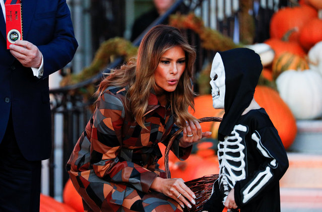 U.S. first lady Melania Trump reacts to a young trick-or-treater dressed as a skeleton as the first lady and the president hand out Halloween candy to visiting schoolchildren in advance of Halloween at the White House in Washington, U.S., October 28, 2019. (Photo by Tom Brenner/Reuters)