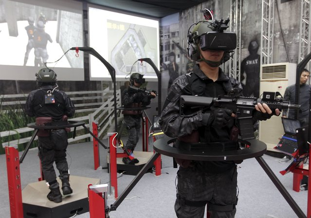 Soldiers display a Taiwan-made immersive interaction i2s3 shooting simulation system at the Taipei World Trade Centre during the 2015 Taipei Aerospace and Defense Technology Exhibition, August 12, 2015. (Photo by Pichi Chuang/Reuters)