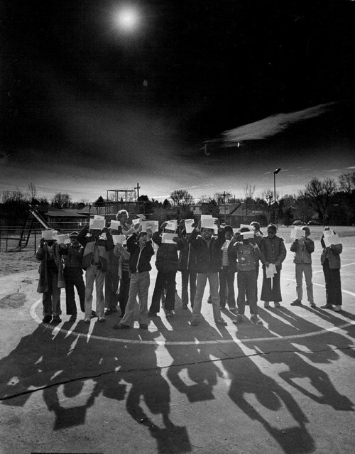 Pupils At Stephen Knight School view the solar eclipse in 1979. They let sun shine over their shoulders and look at image projected through small hole of paper onto another paper. (Photo by Ernie Leyba/The Denver Post)