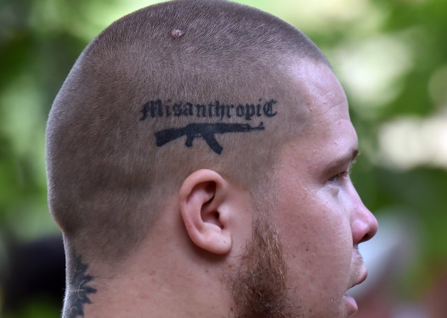 "A recruit to the ""Azov"" far-right Ukrainian volunteer battalion, supports a tattoo on his scalp depicting a Kalashnikov and the word ""Misanthropic"" as he takes part in their competition in Kiev, on August 14, 2015 prior leaving to the battle fields of eastern Ukraine. Two people were killed in another round of intense shelling between Western-backed Ukrainian government's forces and pro-Russian fighters in the separatist east, officials from both sides said. (Photo by Sergei Supinsky/AFP Photo)"