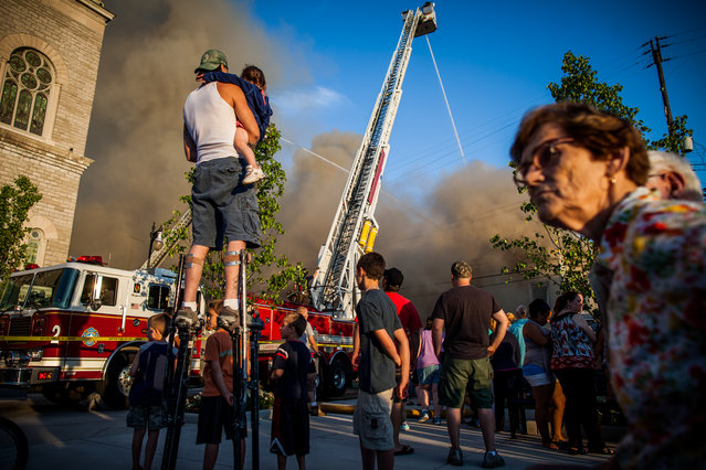 In this July 24, 2014 photo, Nicholas Bowers watches an apartment fire from atop a pair of stilts in Grand Rapids, Mich. No injuries are reported following the Thursday evening fire, which sent smoke billowing into the air that was visible from far away. (Photo by Zach Gibson/AP Photo/The Grand Rapids Press)