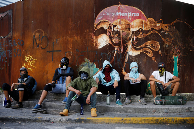 "Protesters sit underneath a graffiti with the writing ""Last lies"" during a rally against Venezuela's President Nicolas Maduro's government in Caracas, Venezuela, June 26, 2017. (Photo by Ivan Alvarado/Reuters)"