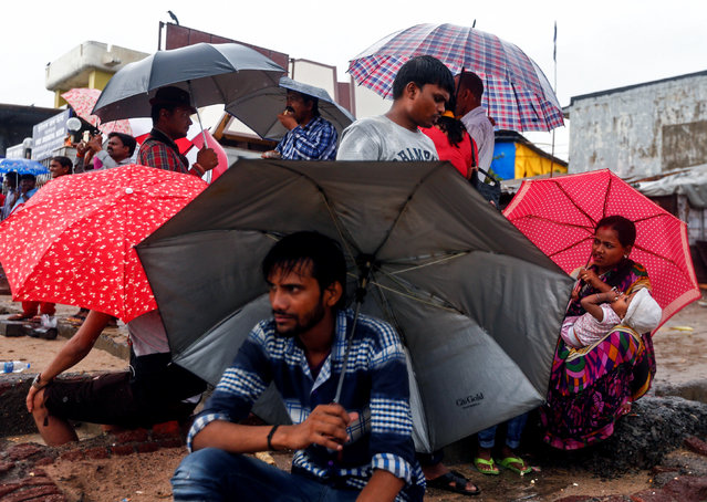 People shelter from the rain under umbrellas on a beach along the Arabian Sea in Mumbai, India June 27, 2016. (Photo by Danish Siddiqui/Reuters)