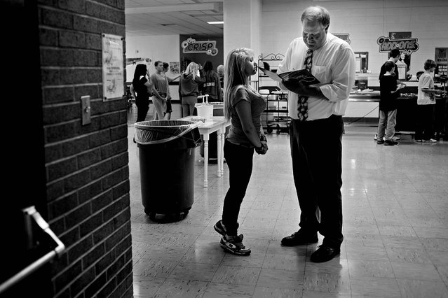 Photojournalist Of The Year (Small Markets). One of 32 pictures in the portfolio of Sean Proctor, of the Midland Daily News:  Standing on her tip-toes to get a better view, Brandi Porter watches as principal Steve Poole writes in her yearbook during eighth grade lunch at Central Middle School in Midland, Mich. Population shrinkage and declining enrollment led to the school's shutdown, with most students and faculty transferring to other schools in the district. (Photo by Sean Proctor)