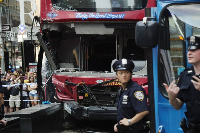 New York Police Department officers stand at the scene of a collision between two tour buses in the Times Square region of New York August 5, 2014. (Photo by Mike Segar/Reuters)