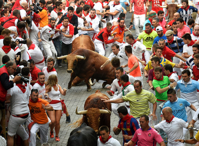 Runners sprint alongside Pedraza de Yeltes fighting bulls near the entrance to the bullring during the fourth running of the bulls at the San Fermin festival in Pamplona, northern Spain, July 10, 2016. (Photo by Eloy Alonso/Reuters)