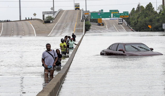 Evacuees wade down a flooded section of Interstate 610 as floodwaters from Tropical Storm Harvey rise Sunday, August 27, 2017, in Houston. The remnants of Hurricane Harvey sent devastating floods pouring into Houston Sunday as rising water chased thousands of people to rooftops or higher ground. (Photo by David J. Phillip/AP Photo)