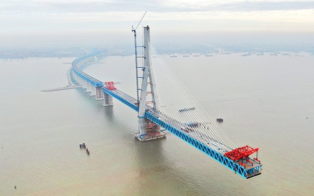 View of the steel truss girder of the world's longest cable-stayed bridge, the Hutong (Shanghai-Nantong) Yangtze River Bridge, under construction on the Yangtze River in Nantong city, east China's Jiangsu province, 29 May 2019. The steel truss girder of Hutong Yangtze River Bridge reached the closure gap in Nantong city, east China's Jiangsu province, on Tuesday (28 May 2019). Spanning 1,092 meters, the bridge is the world's longest cable-stayed bridge for dual-use, with rails on the lower layer and a highway on the top. The bridge is expected to be completed in late 2019. (Photo by Imaginechina via AP Images)