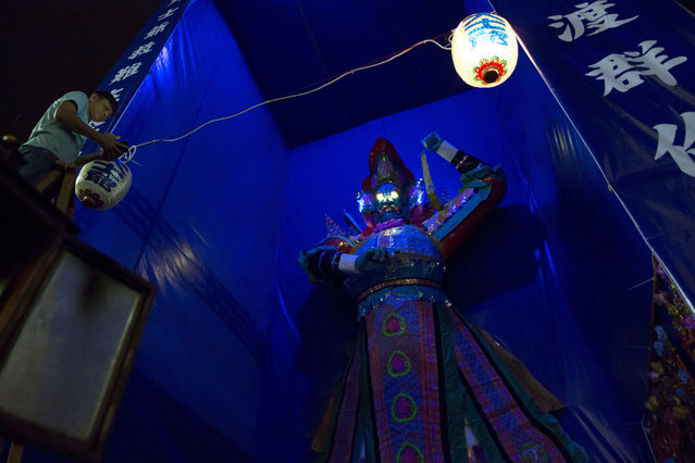 """In this August 31, 2017, photo, a man hangs a lantern in front of a paper reproduction of the """"Ghost King"""" at a makeshift altar during the """"Hungry Ghost Festival"""" in Hong Kong. Countless hungry and restless ghosts are roaming Hong Kong, and the world, to visit their living ancestors, at least according to Chinese convention. In traditional Chinese belief, the seventh month of the lunar year is reserved for the Hungry Ghost festival, or Yu Lan, a raucous celebration marked by feasts and music. (Photo by Kin Cheung/AP Photo)"""