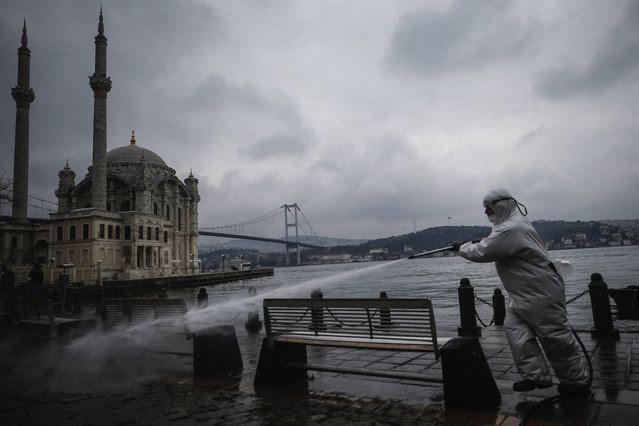 A municipality worker wearing a protective suit sprays water, backdropped by the Ottoman-era Mecidiye mosque and the July 15th Martyrs bridge, formerly known as Bosporus Bridge, over the Bosporus Strait, separating Europe and Asia, in Ortakoy square in Istanbul, amid the coronavirus outbreak, Monday, March 23, 2020. (Photo by Emrah Gurel/AP Photo)