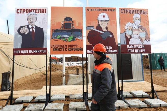 """A construction worker walks past motivational placards designed in the style of Soviet propaganda posters at a construction site where a new hospital is being built on the outskirts of Moscow, Russia on March 21, 2020. The placard (L) depicting Mayor of Moscow Sergei Sobyanin reads: """"Builders! Every minute counts!"""". (Photo by Kirill Zykov/Moscow News Agency/Handout via Reuters)"""