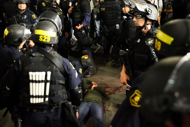 Police officers surround a supporter of conservative commentator Ben Shapiro after she took a fall to the ground following a speech by Shapiro, September 14, 2017 at the University of California, Berkeley. (Photo by Elijah Nouvelage/AFP Photo)