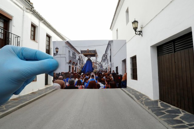 """A Reuters photographer holds a picture of penitents of the """"Cristo Resucitado y Nuestra Senora de Loreto"""" brotherhood taken in April 2019, in front of the street where the procession took place, on Palm Sunday, the first day of Holy Week, amid the coronavirus disease (COVID-19) outbreak, in Ronda, southern Spain, April 5, 2020. (Photo by Jon Nazca/Reuters/Illustration)"""