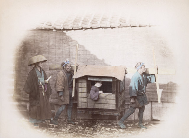 Two Japanese kago bearers carrying a woman in a sedan chair, circa 1865. A samurai with two swords accompanies the group. (Photo by Felice Beato/Spencer Arnold)