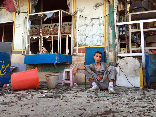 A boy, in a state of shock, sits near the scene of a suicide bomb attack that targeted a demonstration of Hazara minority in Kabul, Afghanistan, 23 July 2016. According to reports at least 20 people were killed and more than 150 injured when a bomb exploded as thousands of people from Hazara minority were protesting the proposed route of the Turkmenistan, Uzbekistan, Tajikistan, Afghanistan, and Pakistan (TUTAP) power line, calling on the government to re-route the line through Bamiyan province which has a majority of Hazara population. The government says the proposed route saves millions of dollars in cost. (Photo by Hedayatullah Amid/EPA)