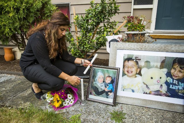 Nissy Koye, friend of Tima Kurdi, the sister of Syrian refugee Abdullah Kurdi whose sons Aylan and Galip and wife Rehan were among 12 people who drowned in Turkey trying to reach Greece, lights a candle near photographs of the boys outside Tima's home in Coquitlam, British Columbia September 3, 2015. (Photo by Ben Nelms/Reuters)