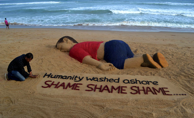 Indian artist Sudarsan Pattnaik works on a sand sculpture depicting drowned Syrian boy Aylan Kurdi at Puri beach, some 65 kilometers away from Bhubaneswar, on September 4, 2015. Charities helping refugees saw a surge in donations on September 4 across Europe as people shocked by the heart-rending images of a drowned Syrian boy on a Turkish beach dug deep to help out. (Photo by Asit Kumar/AFP Photo)