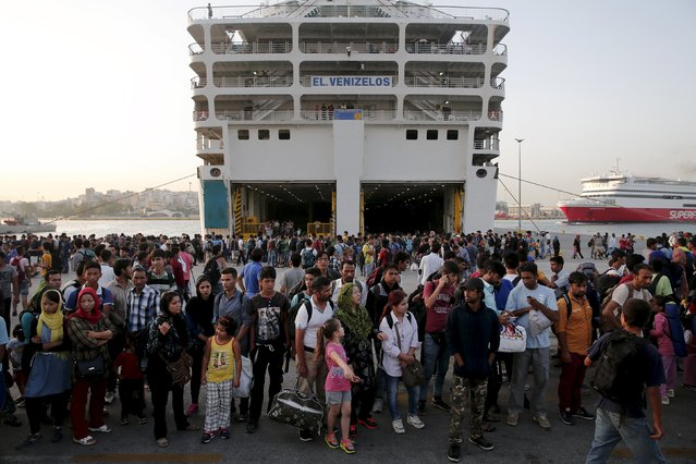 Refugees and migrants wait to board a bus following their arrival onboard the Eleftherios Venizelos passenger ship at the port of Piraeus, near Athens, Greece September 7, 2015. (Photo by Alkis Konstantinidis/Reuters)