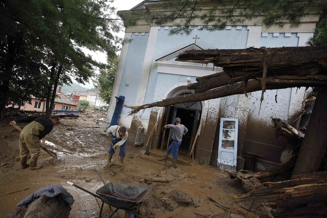 People clean the mud outside a church after heavy floods in Tekija village September 17, 2014. (Photo by Djordje Kojadinovic/Reuters)