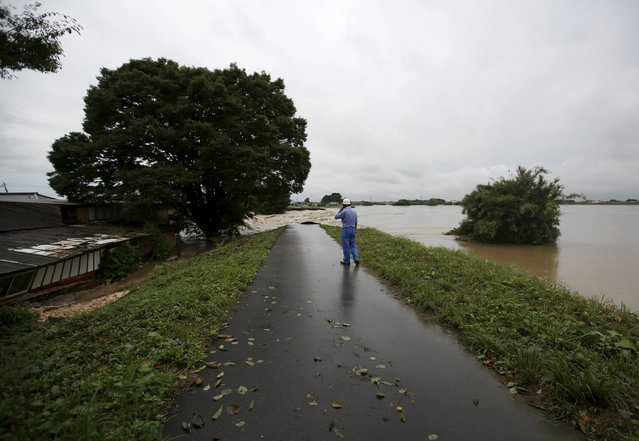 A man looks at floodwaters at a break in the dike of the Kinugawa river (R) at a residential area flooded by the river, caused by typhoon Etau, in Joso, Ibaraki prefecture, Japan, September 10, 2015. (Photo by Issei Kato/Reuters)